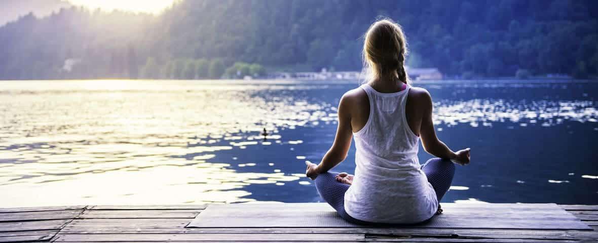 Frau macht Yoga am See