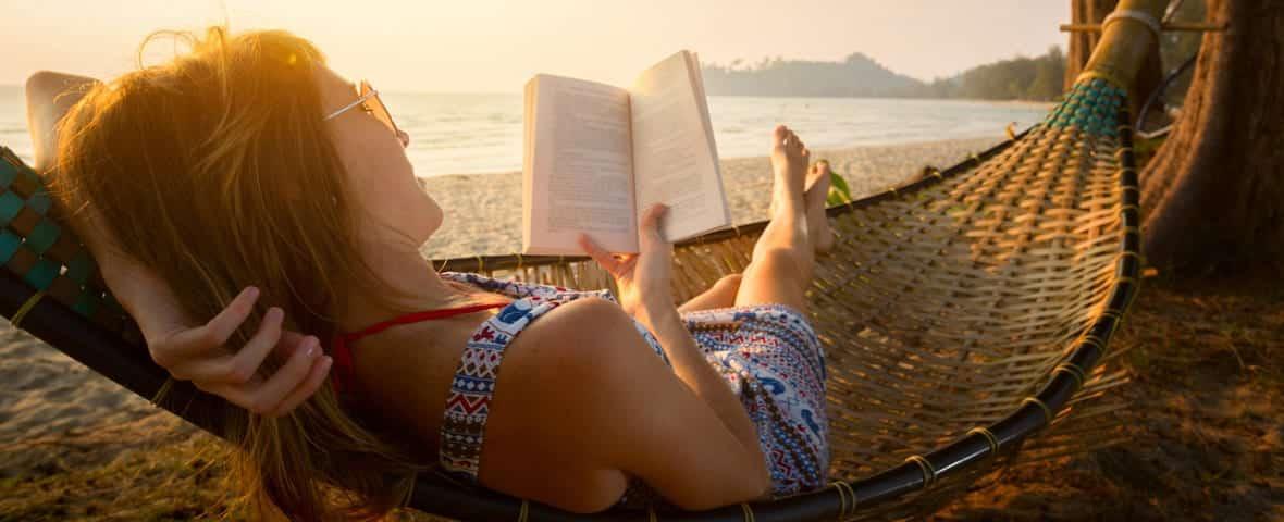 Frau entspannt in Hängematte mit Buch